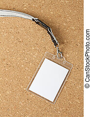 Blank badge with neckband on corkboard background.