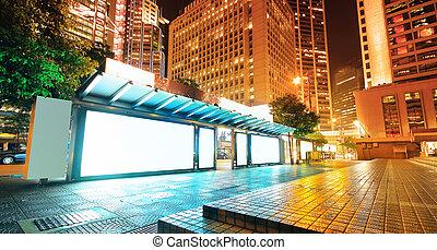 Blank billboard on bus stop at night