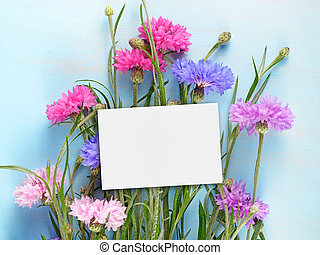 Blank birthday card and cornflowers on blue wooden background