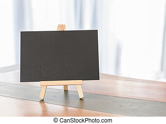 Blank black board on wooden desk in white room