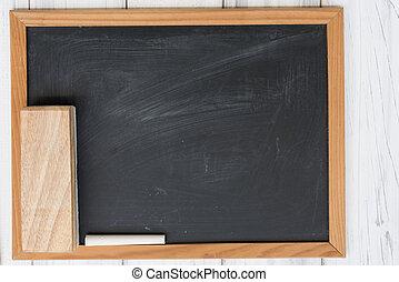Blank black board, white chalk and eraser on grunge wooden background