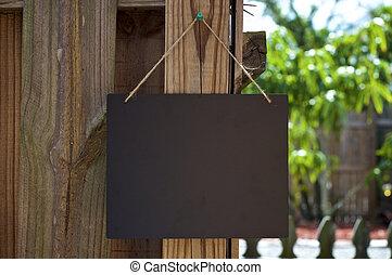 blank black chalkboard hanging outdoors