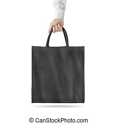 Blank black cotton eco bag design mockup isolated, holding hand, clipping path. Textile cloth bag mock up template hold arm. Tote shoe consumer reusable organic craft package. Carrier recycle bag