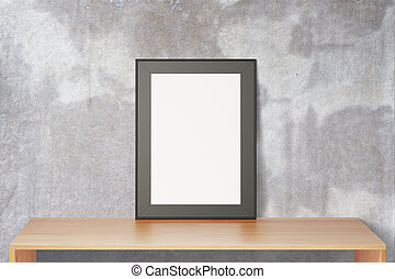 Blank black picture frame on wooden table and concrete wall, mock up
