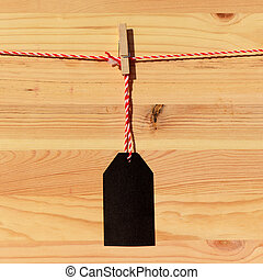 Blank black price tag on the background of wooden planks