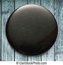 Blank black round badge on wood
