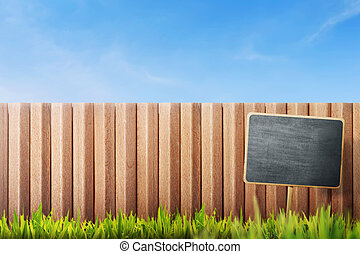 Blank black sign board on grass