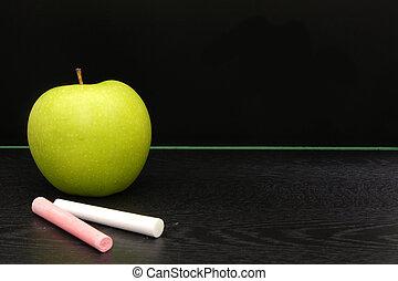 Blank blackboard - Teachers apple and chalk on a desk in ...