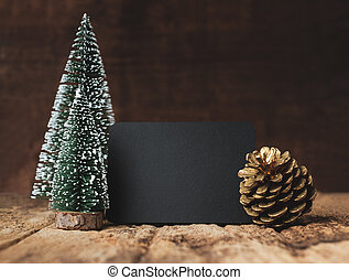 Blank blackboard with christmas tree and gold pine cone and snow falling on grunge wood table and dark brown wooden wall. winter holiday greeting card mock up template.