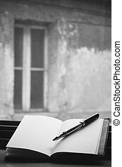 An old blank book on a windowsill with a pen on the right side. In the background an out of focus old building with a window.
