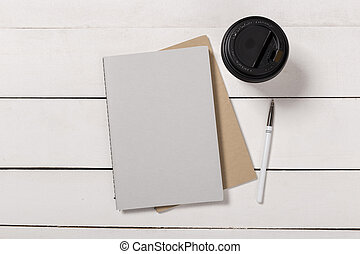Blank book cover template with page in front side standing on white wood background flat lay.