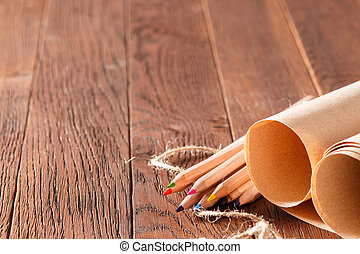 Blank brown paper and color pencils on wooden table with decorative rope