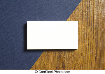 Blank business cards half of each lie down on blue textured paper and wooden desk background, with 3.5 x 2 inches size as template for design presentation, showcase etc.