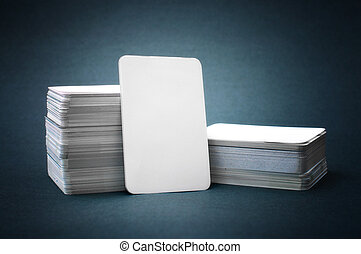 The pile of blank business cards lays propped up another business card.