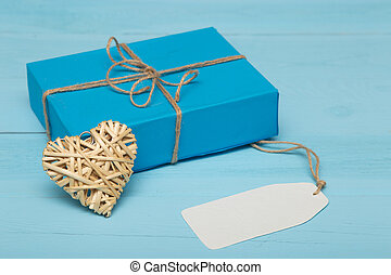 blank card, gift with straw heart on a blue background