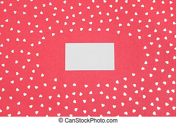 Blank card on pink background with shiny hearts