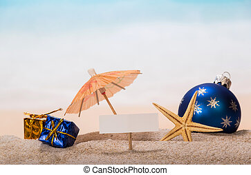 Blank card, starfish, gifts, Christmas ball in sand against sea.