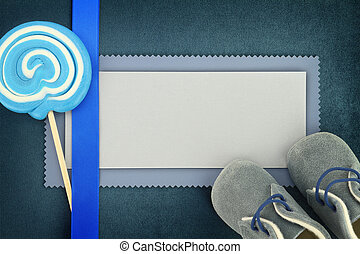 Blank card with lollipop and baby shoes on blue background