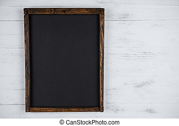 Blank chalkboard on white wooden background with copy space