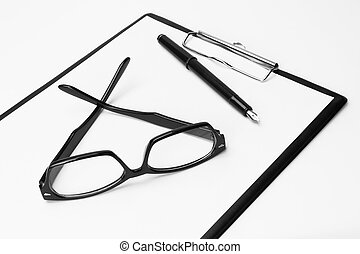 Blank clipboard with pen and eyeglasses