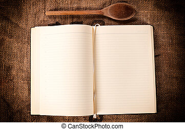 Blank cookbook and wooden ladle on abstract background