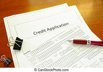 Blank credit application form with pen and clips