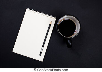 white paper notepad and a cup of coffee on black chalkboard back