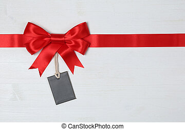 Blank gift tag with bow for gifts on a wooden background