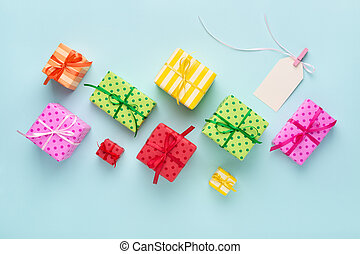 Blank gift tag with ribbon & colorful gift boxes.