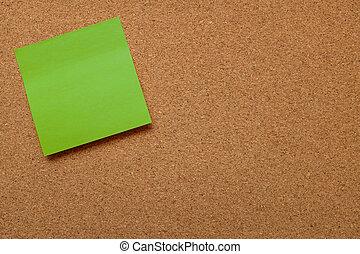 Blank green note paper stuck on cork board