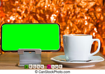 Blank green screen on cell phone and wood dice .
