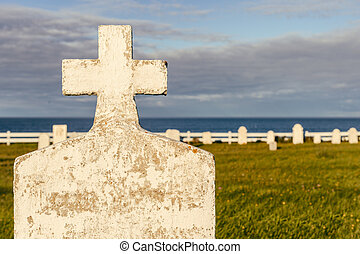 Blank headstone in a cemetery, with ocean in the background, at sunset