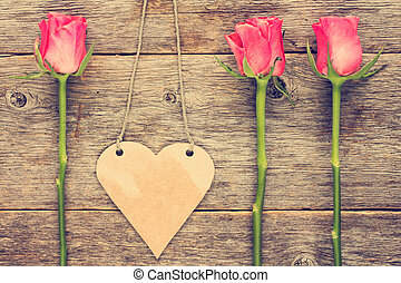 Blank heart shaped tag and three roses