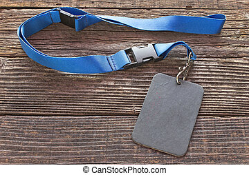 Blank ID card tag with blue ribbon on wooden background