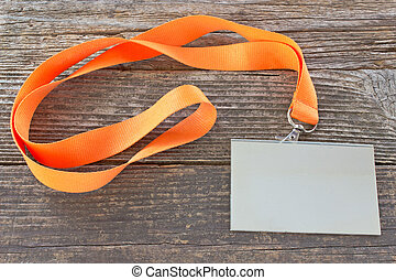 Blank ID card tag with ribbon on wooden background