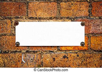 Blank information board on brick wall