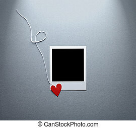 Blank instant photo and small red paper heart with white...