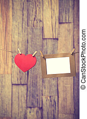 blank instant photos hanging on the clothesline with red...