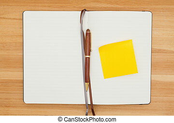 Blank journal with pen and a yellow sticky note on a wood desk