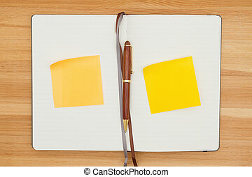 Blank journal with pen and yellow sticky notes on a wood desk
