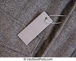 Blank label price tag mockup on brown coat.