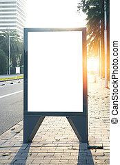 Blank lightbox on the city streets. Vertical. Sunlights effects