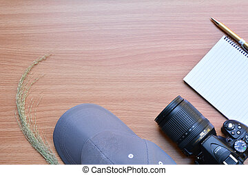 Blank memory book with pen, cap and camera on wooden table.