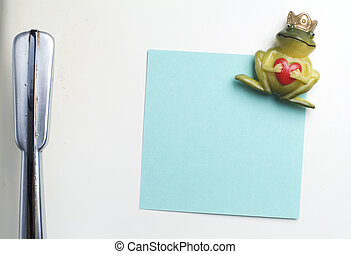 Blank note on fifties fridge-door, close-up of frog with crown holding a heart magnet