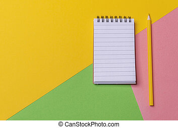 Blank notebook and a pencil on a colorful desk. Above view. Minimalist style.