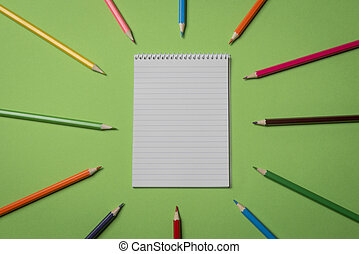 Blank notebook and colored pencils on a green background. Above view