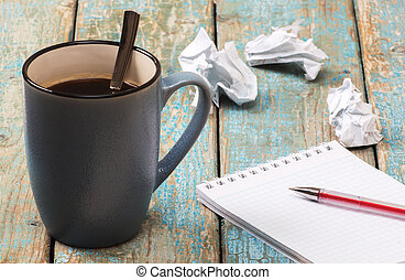 Blank notebook and cup of coffee on the wooden table