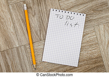 Blank notebook and pencil with todo list on a wooden...