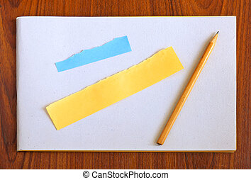 Blank notebook and pencil with torn paper on wooden background