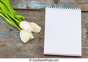 Blank notebook mock up for artwork with white tulips. Place for text. Fresh flowers on old wooden background